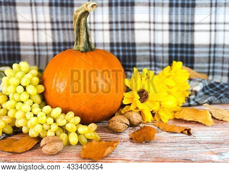 Festive Autumn Decor. Autumn Composition With Pumpkin, Yellow Flowers And Grape. Happy Thanksgiving.