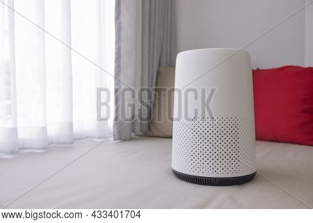White Air Purifier Sits In The Living Room With White Curtains And Red-brown Pillows In The Backgrou