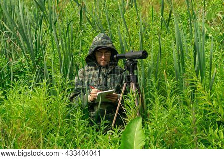 Man Ornithologist Records The Results Of The Observations While Standing Among The Tall Grass In The