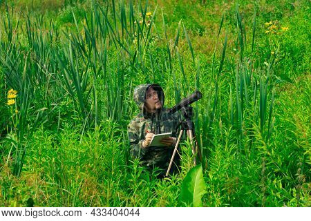 Man Wildlife Researcher Records The Results Of The Observations While Standing Among The Tall Grass