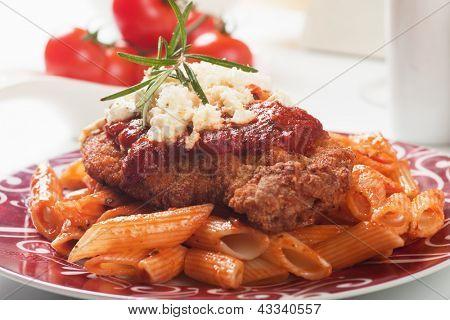 Chicken parmesan, breaded chicken steak with tomato sauce and macaroni pasta