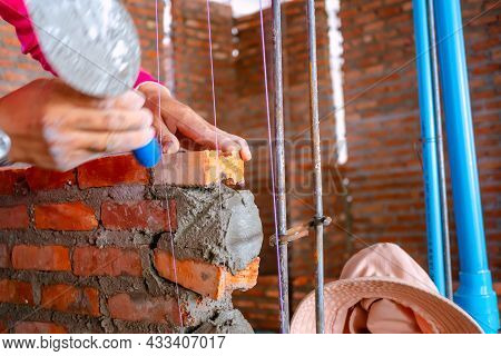 Buildings Are Built Of Hard Red Brick And Are Very Long-lasting. Worker Installing Red Brick For Con