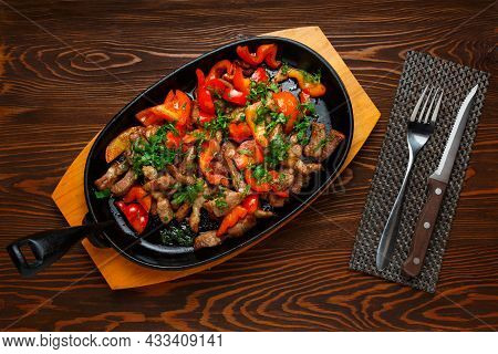 Roast Pork With Red Bell Pepper In A Frying Pan On A Dark Wooden Table, Knife, Fork, Top View