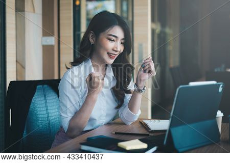 Excited Asian Woman Sits At Her Workstation, Ecstatic To Have Received A Job Offer Following An Inte