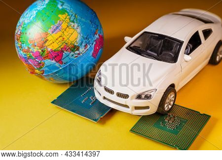 Close Up View Of A White Toy Car On Top Of A Microprocessor And A World Globe.