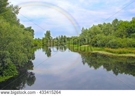Bright Rainbow In The Sky With Clouds Above River. Multicolored Rainbow Above Quiet River. Beautiful