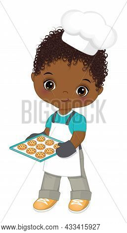 Cute Little African American Boy Wearing Chefs Toque, Oven And Apron Holding Baking Tray With Cookie