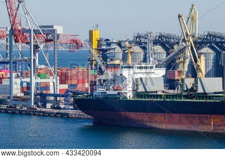 Port Cargo Crane Loads A Container Onto A Cargo Ship In A Seaport.