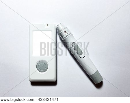 A Blood Glucose Meter With A Mockup And A Pen For Piercing Fingers. Measurement Of Glucose Levels