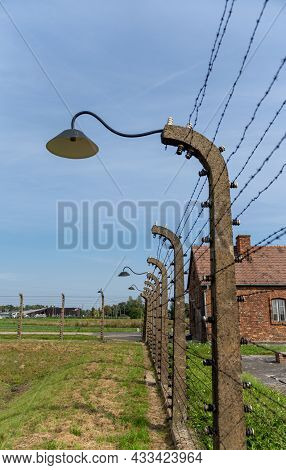 Barbed Wire Fence And Lanterns With Guard House In The Background At The Auschwitz Concentration Cam