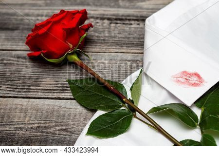 A Trace Of Lipstick Lips From A Kiss On Men's Clothing. One Red Rose Lies On A White Shirt On A Roug