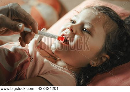 Father Giving Medicine To Sick Child With Syringe.