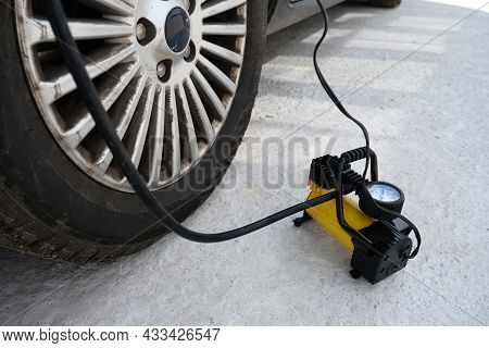 The Deflated Car Wheel Is Inflated By An Electric Compressor, Car Accident Concept