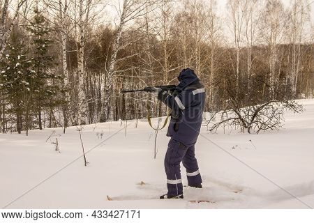 A Hunter Or Poacher Stands On Skis At The Edge Of The Forest And Aims His Weapon At Prey