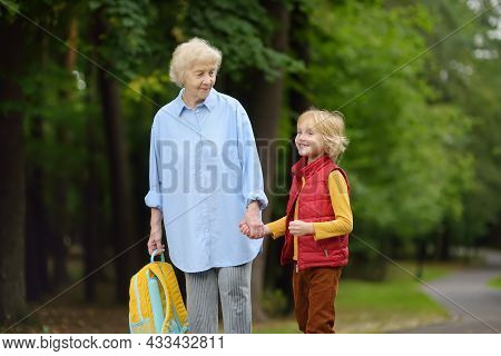 Beautiful Gray-haired Elderly Lady Accompanies Or Pick Up Baby From School Or Preschool. Friendship