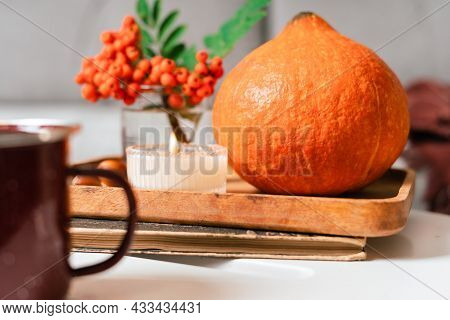 Still Life Book, Candle, Rowan Berry, Pumpkin And A Cup Of Tea Or Coffee In The Living Room On A Tab
