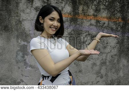 Happy And Smile Face With Smile Of Young Asian Girl With Hand Point On Empty Space.