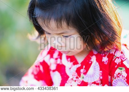 Close Up, Adorable 1-2 Year Old Asian Girl Is Looking Down At Her Path. A Cheerful Baby Wears A Red