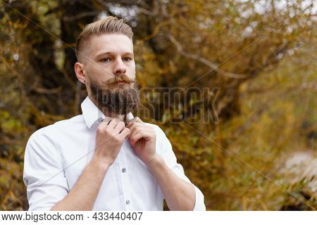 Portrait Of Pensive Bearded Attractive Young Man In White Shirt Looking Over An Autumn Park In Octob