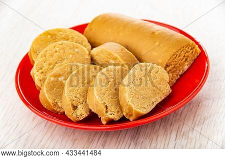Sweet Creamy Sausage With Peanut (oriental Sweets), Slices Of Sweets In Red Saucer On Wooden Table