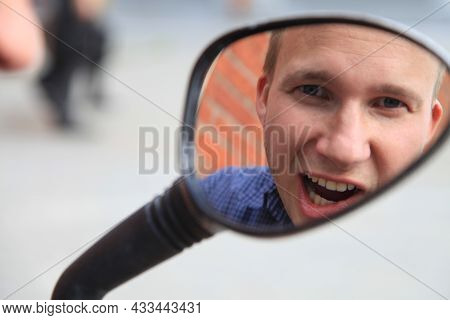Portrait Of A Man In A Mirror Image.a Comical, Cheerful, Cheerful Guy In The Mirror From A Motorcycl