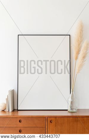 Blank large frame on a wooden sideboard in a living room