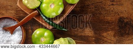 Tomatillos, Green Tomatoes, Panorama With A Place For Text. Mexican Cuisine Ingredients On A Dark Ru