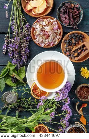 Tea With Herbs, Flowers And Fruit, Shot From The Top On A Dark Rustic Wooden Background