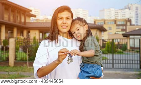 Cheerful Woman Shows Keys Of New Apartment Holding Little Korean Daughter In Arms Against Detached H