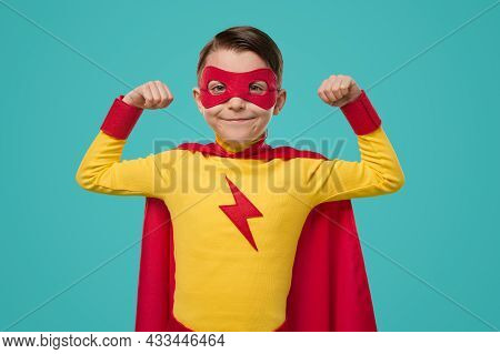 Brave Little Boy In Bright Yellow And Red Superhero Costume With Cape And Mask Demonstrating Strengt