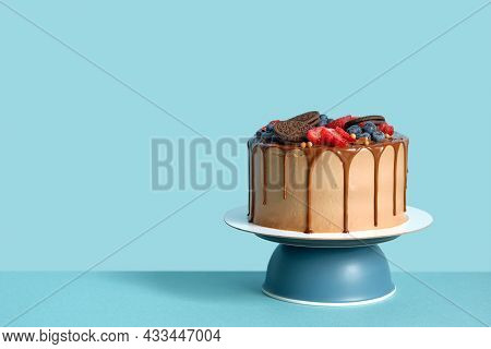 Chocolate Birthday Cake With Berries And Cookies On Blue Wall Table Background, Copy Space