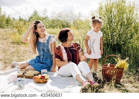 A Grandmother And Her Two Granddaughters Have A Picnic In Nature, Spend Time Together On Weekends