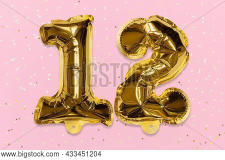 The Number Of The Balloon Made Of Golden Foil, The Number Twelve On A Pink Background With Sequins.