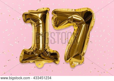The Number Of The Balloon Made Of Golden Foil, The Number Seventeen On A Pink Background With Sequin