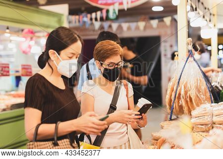 Female Customer In Protective Mask Make Contactless Mobile Payment In Retail Shop