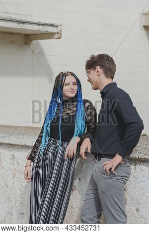 A Man Is Flirting With A Woman. A Couple Of Young People Are Standing At A High Concrete Parapet. A