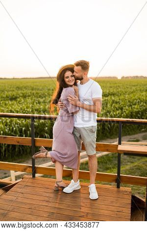 Beautiful Joyful Couple Standing At The Field, Hugging, Having A Date In Sunset, Enjoying Moments To
