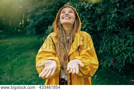 Image Of A Positive Young Blonde Woman Smiling Wearing Yellow Raincoat During The Rain In The Park.
