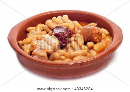 closeup of a earthenware plate with fabada asturiana, a typical spanish bean stew, on a white background