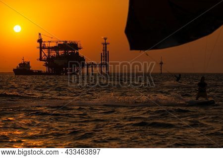 Extreme Sport Kitesurfing against Offshore Jack Up Rig in The Middle of The Sea at Sunset Time