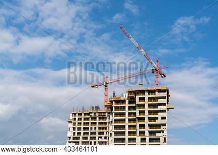 Construction Site With A Concrete High-rise Skyscraper Building And Scaffolding And Two Cranes On To