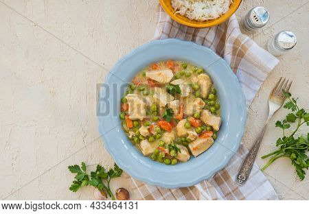 Chicken Stew Or Indian Curry With Carrots And Green Peas In A Gray Plate On A Light Concrete Backgro