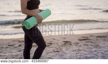 Playing Sports On The Shore Of The Sea At Dawn. The Girl Does Yoga On The Sand By The Sea.