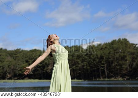 Excited Woman In Green Dress Stretching Arms Screaming To The Air In A Lake