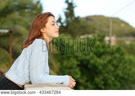 Side View Portrait Of A Woman Contemplating Views From Balcony Of Rural House