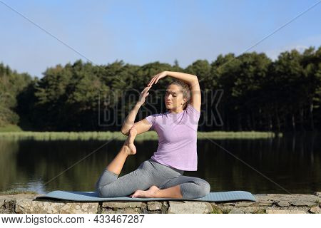 Full Body Portrait Of A Woman Doing Yoga Advanced Pose In A Lake On Summer