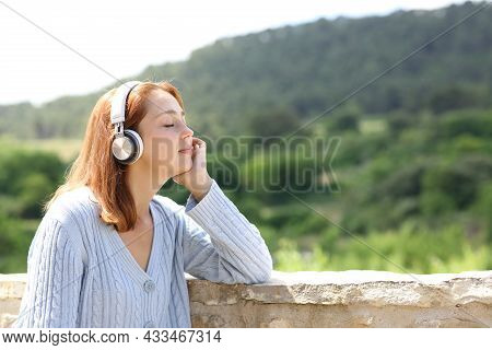 Woman Wearing Wireless Headphones Resting Listening To Music In A Balcony In A Rural House