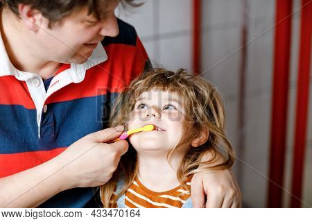 Father Helping His Little Daughter With Brushing Teeth. Little Toddler Girl And Dad In Bathroom, Mak