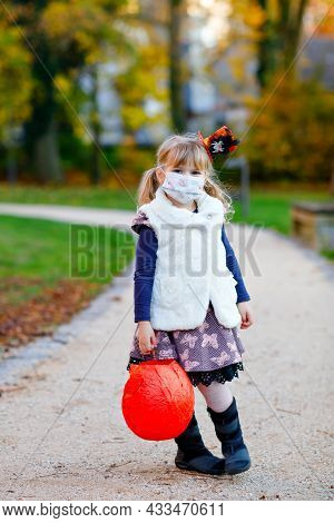 Little Toddler Girl Dressed As A Witch With Medical Mask On Face Trick Or Treating On Halloween. Chi