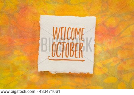Welcome October greeting note  - handwriting on a handmade rag paper against marbled paper, calendar concept
